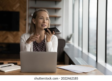 Happy business woman recording audio message on cellphone at workplace, making phone call on speaker, giving audio command to virtual assistant for online search, using voice recognition app