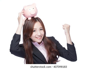 Happy Business woman show fist and holding pink piggy bank isolated on white background. Asian woman