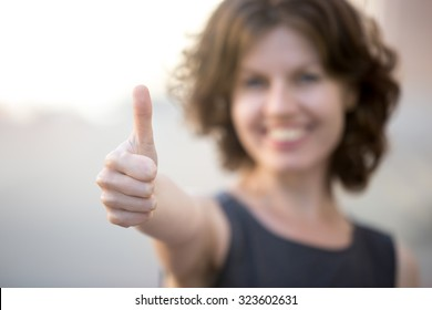 Happy business woman showing thumbs up, standing on the street in summer, friendly smiling, focus on hand