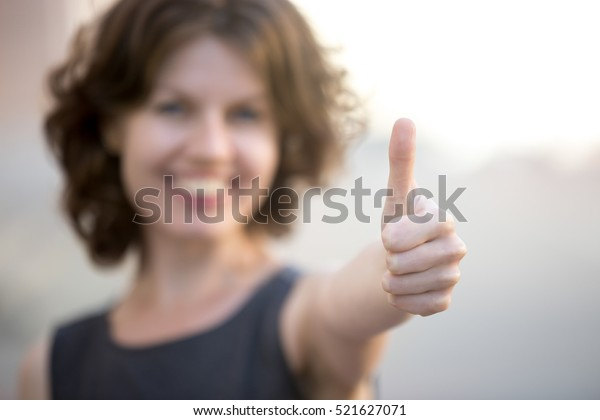 Happy business woman showing thumbs up, standing on the street in summer, friendly smiling, focus on hand. Recommendation concept
