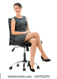 Happy business woman sitting on a chair - isolated over white background