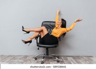Happy business woman sitting on chair with raised arms and having fun isolated over gray background