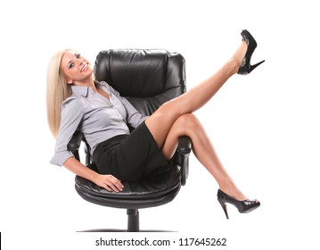 A happy business woman sitting in a swivel chair with her legs up in the air isolated on white.