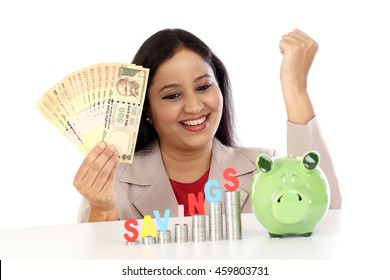 Happy business woman with stack of coins and holding rupee notes