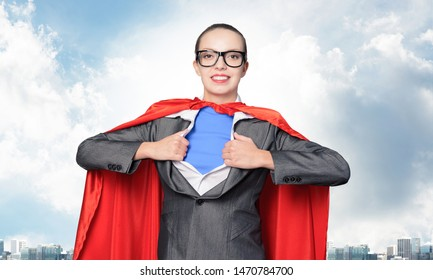 Happy business woman tearing off her shirt and transforming in super heroine. Smiling business lady in glasses with red hero cape on blue sky background. Brave super woman ready for new achievements.