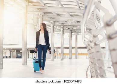 Happy business woman is traveling with luggage in airport