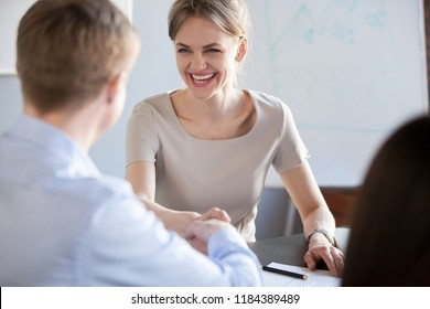 Happy business woman with wide smile laughing handshaking new male partner after signing contract satisfied with negotiations positive result, making good partnership deal or getting hired concept