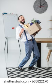 happy businessman with cardboard box in hands quitting job