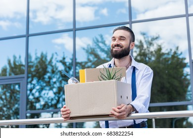 happy businessman with cardboard box with office supplies in hands standing outside office building, quitting job concept