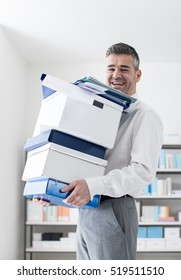 Happy businessman carrying boxes and paperwork in the office, he is smiling at camera, relocation and efficiency concept