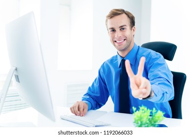 Happy businessman in confident clothing, blue shirt and tie, showing two fingers or victory gesture, working with desktop computer at office. Success in business, job and education concept.
