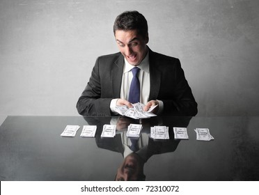 Happy businessman counting out some banknotes