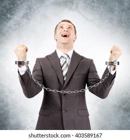 Happy businessman in cuffs