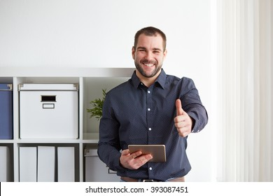 Happy businessman with digital tablet makes a gesture thumb up in the office
