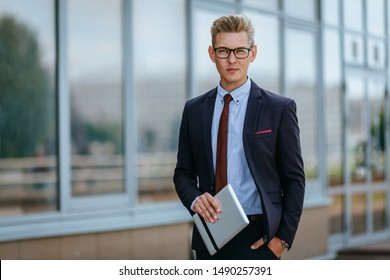Happy businessman with digital tablet. Portrait of a Male executive manager in trendy clothes with tablet PC in hand on background of office building. Modern technology concept