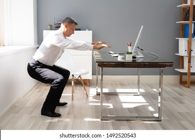 Happy Businessman Doing Squats Exercise In Front Of Computer At Office