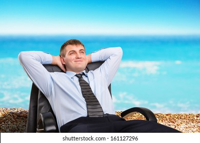 Happy businessman dreaming about vacation sitting in a chair
