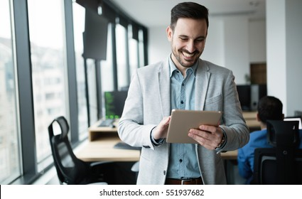 Happy businessman dressed in suit in modern office using tablet
