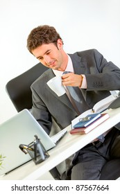 Happy businessman drinking coffee and looking in laptop