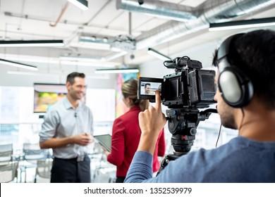 Herzlichen Glückwunsch Geschäftsmann während des Interviews mit Journalistinnen. Manager beantwortet Fragen im Büro. Junge Frau als Reporterin mit Geschäftsmann und Kameramann, die Video für die Sendung gedreht hat