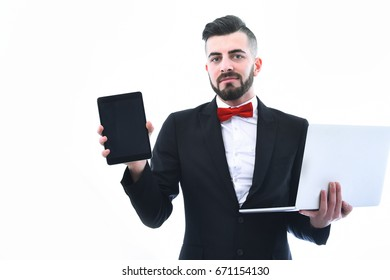 Happy businessman or executive director with beard and smile holds modern tablet and laptop, wears red bow. Isolated on white background, concept of presentation and online business conference