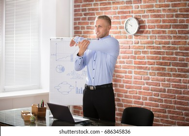 Happy Businessman Exercising During Break In Modern Office