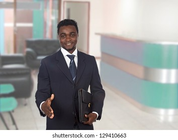 Happy businessman extending his hand for greeting in the office