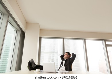 Happy businessman finished working day, satisfied with all office tasks done, resting after laptop work with feet up on desk, relaxing while business apps doing job, having passive income, copy space