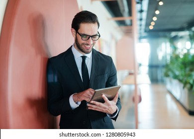 Happy businessman in formal wear standing against the wall in business center and using tablet for reading e-mail.