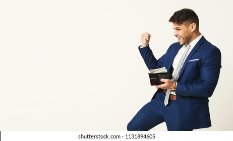 Happy businessman with full money wallet. White studio background, copy space