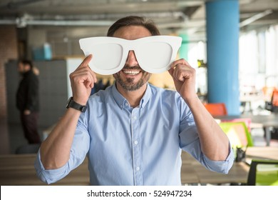 Happy businessman with funny glasses on showing to camera. Handsome happy man joking during work. Break time concept.