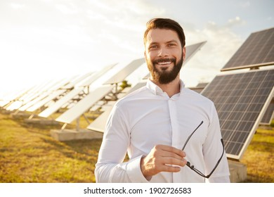 Happy businessman with glasses smiling and looking at camera while standing against photovoltaic panels on solar power station