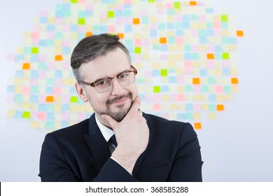 Happy businessman in glasses touching his chin on light background