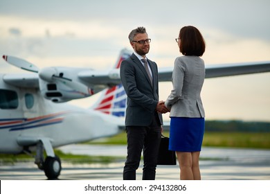 Happy businessman handshaking with his partner on background of airplane