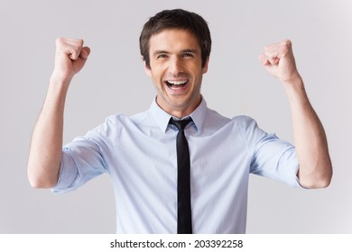 Happy businessman. Handsome young man in shirt and tie gesturing and smiling while standing against grey background