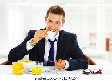 happy businessman having breakfast at office