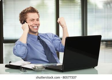 Happy businessman hearing good news on phone