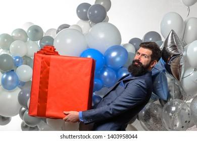 Happy businessman with helium balloons holds big gift box. Bearded man with present box. Stylish business man with inflatable air balloons holds gift box. Happy birthday, holidays, celebration, party.