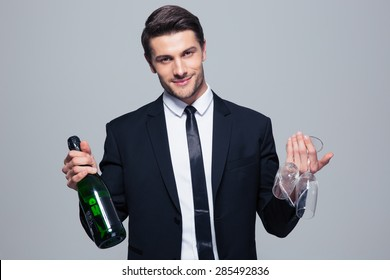 Happy businessman holding bottle with champagne and glass over gray background