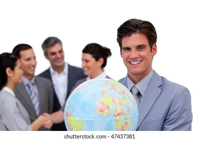 Happy businessman holding a globe in front of his team against a white background