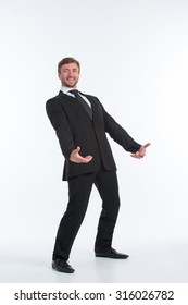Happy businessman holding an invisible heavy load on his back isolated on white. Smiling man in black business suit wants to succeed.