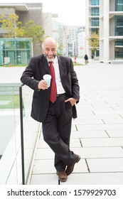 Happy businessman holding paper cup and smiling at camera. Full length view of cheerful mature businessman holding coffee to go and smiling at camera on street. Business concept