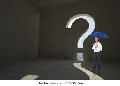 Happy businessman holding umbrella against question mark door in dark room