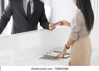 Happy Businessman in Hotel check in at reception or front office being given key card. Classy welcome Concept. Setup studio shooting.