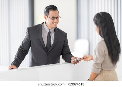 Happy Businessman in Hotel check in at reception or front office being given key card. Classy welcome Concept? Setup studio shooting.