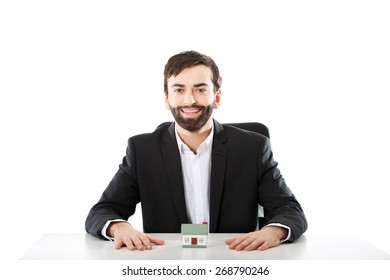 Happy businessman with a house model in the office.