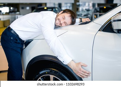 Happy businessman hugging his new car in showroom
