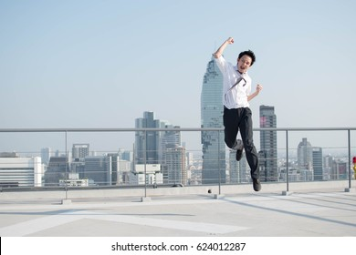 Happy businessman jumping after him work successful on top of building