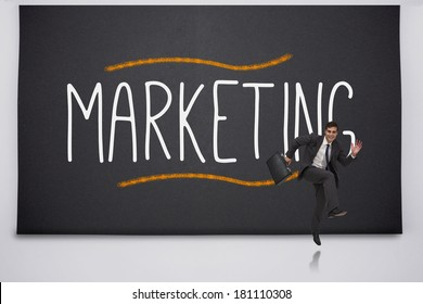 Happy businessman jumping against the word marketing
