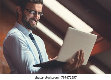 Happy businessman with laptop indoors